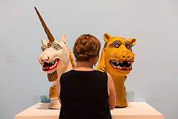 © Licensed to London News Pictures. 08/06/2014. London, UK. A woman looks at unicorn and lion ships' carvings from the 19th century in painted wood at the British Folk Art exhibition at Tate Britain in Millbank, London on 8th June 2014. The British Folk Art exhibition at Tate Britain opens on 10th June 2014 and runs until 31st August 2014. Photo credit : Vickie Flores/LNP
