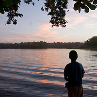 A boy fishes off a dock into the Rio Toruguero, in Tortuguero, Costa Rica on April 8, 2009.  The fishing here is world class, and today many locals work as fishing guides for tourists.  (Photo/William Byrne Drumm)