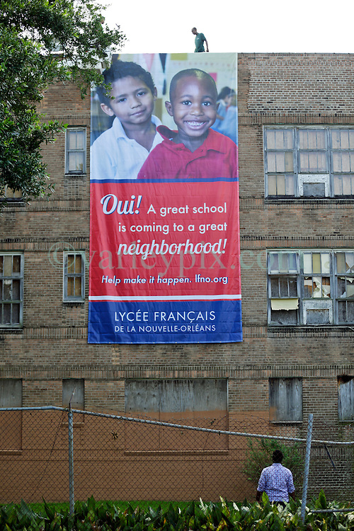 08 August 2015. New Orleans, Louisiana.<br /> Clean up begins at the Alfred C Priestley Junior High School. Lycée Francais installs new fencing, cuts back hazardous trees and hangs a large welcome banner at the derelict old school in Pigeon Town.The last students and teachers left the building in 1980.<br /> Photo; Charlie Varley/varleypix.com
