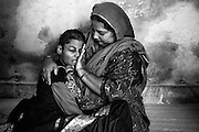 Crying and sick with high fever, Firdaus Haneef, 16, a girl affected by severe cerebral palsy, is being comforted by her mother, Asma, 35, a '1984 Gas Survivor', while sitting on the floor of their home in Bapu Colony, Bhopal, Madhya Pradesh, central India.