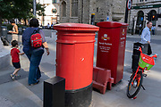 In the week that many more Londoners returned to their office workplaces after the Covid pandemic, an adult and child walk past  red postal boxes and a Lime rental bike in the City of London, the capital's financial district, on 8th September 2021, in London, England.