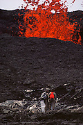 Onlookers watch as lava spews forth from an eruption on the summit of Mauna Loa, Big Island, Hawaii. USA.
