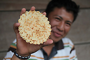 """Philip Bolon, 18, Mopan Mayan member of San Jose community, holds a """"chu kwa"""", or sweet tortilla, during a tea and biscuits break from the reconstruction of the community's Catholic church. Toledo Cacao Growers' Association (TCGA), San Jose, Toledo, Belize. January 25, 2013."""