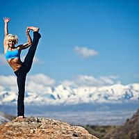 Woman performs Utthita Hasta Padangustasana yoga position in Big Cottonwood Canyon, Utah