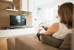 Pregnant woman sitting on sofa and watching TV with remote control, Munich, Bavaria, Germany
