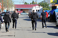 Police officers patrol Soledad Street in Salinas during a sweep of homeless encampments on Thursday, March 24th in the Market Way area of Chinatown.