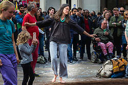 A woman dances barefoot on the compost-strewn centre of Oxford Circus as hundreds of environmental protesters from Extinction Rebellion occupy Oxford Circus, a pink yacht being the focal point of their presence, with traffic denied access to two of London's busiest streets. London, April 16 2019.