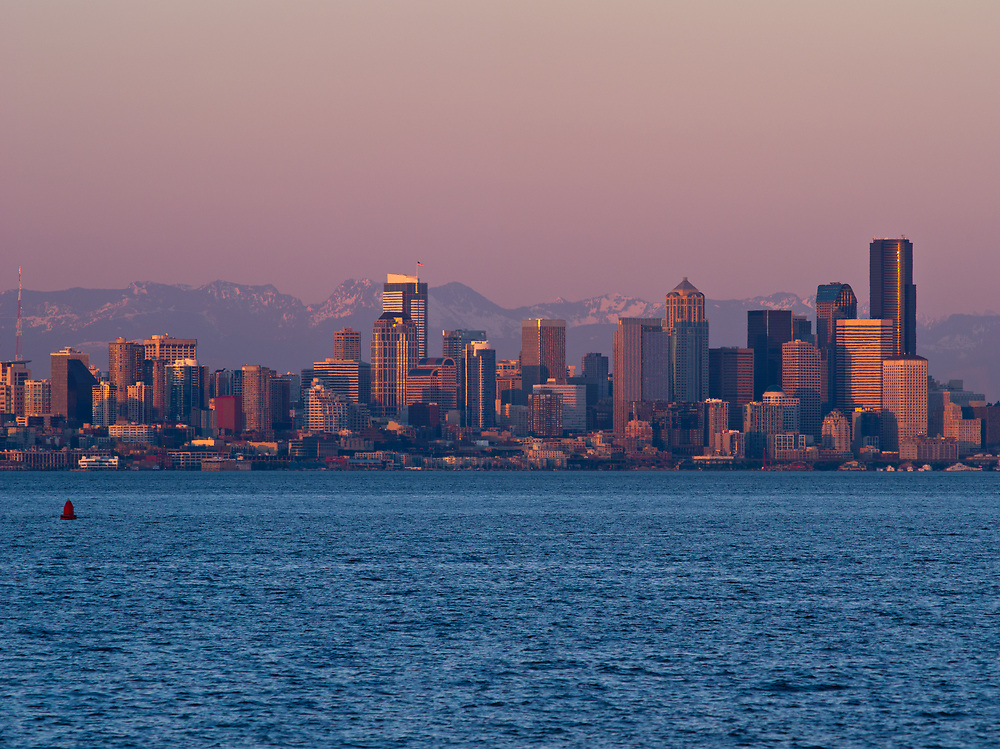 Bathed in warm afternoon light, Seattle's skyline contrasts sharply with the cool tones of Elliot Bay, as seen from Bainbridge Island.