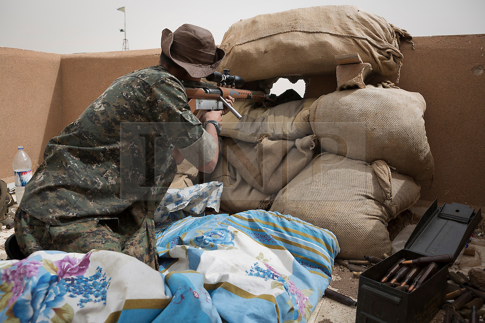 © Licensed to London News Pictures. 28/09/2014. Al-Yarubiyah, Syria. Using a home made 14.5mm rifle, a sniper belonging to Syrian Kurdish YPG forces in Al-Yarubiyah, Syria, aims at Islamic State positions across the border in Rabia, Iraq.<br /> <br /> Facing each other across the Iraq-Syria border, the towns of Al-Yarubiyah, Syria, and Rabia, Iraq, were taken by Islamic State insurgents in August 2014. Since then The town of Al-Yarubiyah and parts of Rabia have been re-taken by fighters from the Syrian Kurdish YPG. At present the situation in the towns is static, but with large exchanges of sniper and heavy machine gun fire as well as mortars and rocket propelled grenades, recently occasional close quarter fighting has taken place as either side tests the defences of the other. Photo credit: Matt Cetti-Roberts/LNP