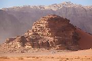 A Jeep drives under high sandstone cliffs in the desert of Wadi Rum, Jordan.
