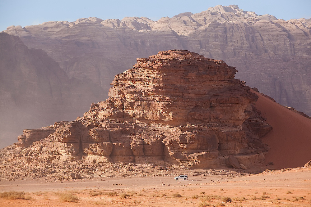 A Jeep drives under high sandstone cliffs in the desert of Wadi Rum, Jordan.