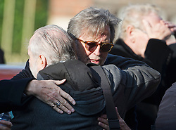 © London News Pictures. 05/11/2014. ERIC CLAPTON hugs another guest while  arriving for the service. The funeral Jack Bruce at Golders Green Crematorium in North London. Jack Bruce was the lead singer and bass player for British Rock band Creme, alongside Eric Clapton and Ginger Baker. Creme sold over 15 million albums worldwide and were widely considered to be the worlds first successful supergroup. Photo credit : Ben Cawthra/LNP