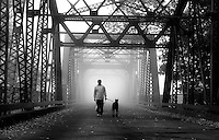 Ray Anderson walks his dog Sir in the fog, on the discover Park bridge. Anderson is from New York, but is here with wis wife for a couple months while she works here temporarily.