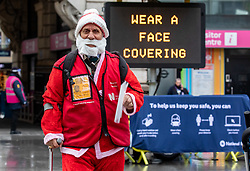 © Licensed to London News Pictures. 14/12/2020. London, UK. Santa walks past an information sign in Westminster, London this afternoon as the government warn that London could be forced into Covid-19 tier 3 restrictions before Christmas as infections increases throughout the capital. Today, Health Secretary Matt Hancock will address the House of Commons with the latest up dates on Covid-19 infections as ministers fear that London is on the brink of moving into tiers 3 before Christmas. Photo credit: Alex Lentati/LNP