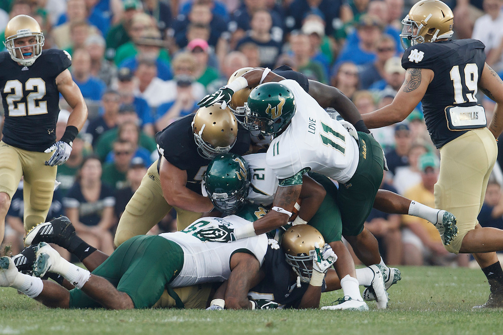South Florida running back Demetris Murray (#21) is tackled by a host of Notre Dame defenders in action during NCAA football game between Notre Dame and South Florida.  The South Florida Bulls defeated the Notre Dame Fighting Irish 23-20 in game at Notre Dame Stadium in South Bend, Indiana.