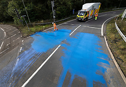 © Licensed to London News Pictures. 17/09/2021. Leatherhead, UK. A Highways England worker examines blue paint on the slip road of junction 9 of the M25 in Leatherhead after climate change protesters stopped traffic. Police have cleared a group of protesters who were blocking the roundabout at the exit of the M25 at junction 9 Leatherhead in Surrey. Photo credit: Peter Macdiarmid/LNP