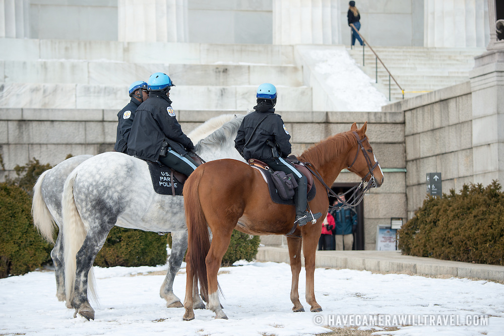 US Park Police on horses patrol the Lincoln Memorial in the snow in Washington DC.