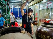 """14 FEBRUARY 2019 - SIHANOUKVILLE, CAMBODIA:  A Chinese woman who operates a Chinese restaurant with her husband checks on soups she bakes in a clay jar. There are thousands of Chinese workers in Sihanoukville who work to support the casino and hotel industry in the town and thousands of other Chinese migrants have moved into Sihanoukville and opened businesses that cater to the workers. There are about 80 Chinese casinos and resort hotels open in Sihanoukville and dozens more under construction. The casinos are changing the city, once a sleepy port on Southeast Asia's """"backpacker trail"""" into a booming city. The change is coming with a cost though. Many Cambodian residents of Sihanoukville  have lost their homes to make way for the casinos and the jobs are going to Chinese workers, brought in to build casinos and work in the casinos.     PHOTO BY JACK KURTZ"""