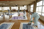 Removing fluff from carpets. Oriental Carpet Mills, Yamanobe-machi, Yamagata, Japan, April 11, 2016. Oriental Carpet Mills was founded in 1935 and produces luxury hand-woven and tufted carpets. Its carpets are used all over the world, including in the Vatican, the Imperial Palace in Tokyo and the Kabukiza Kabuki Theatre.