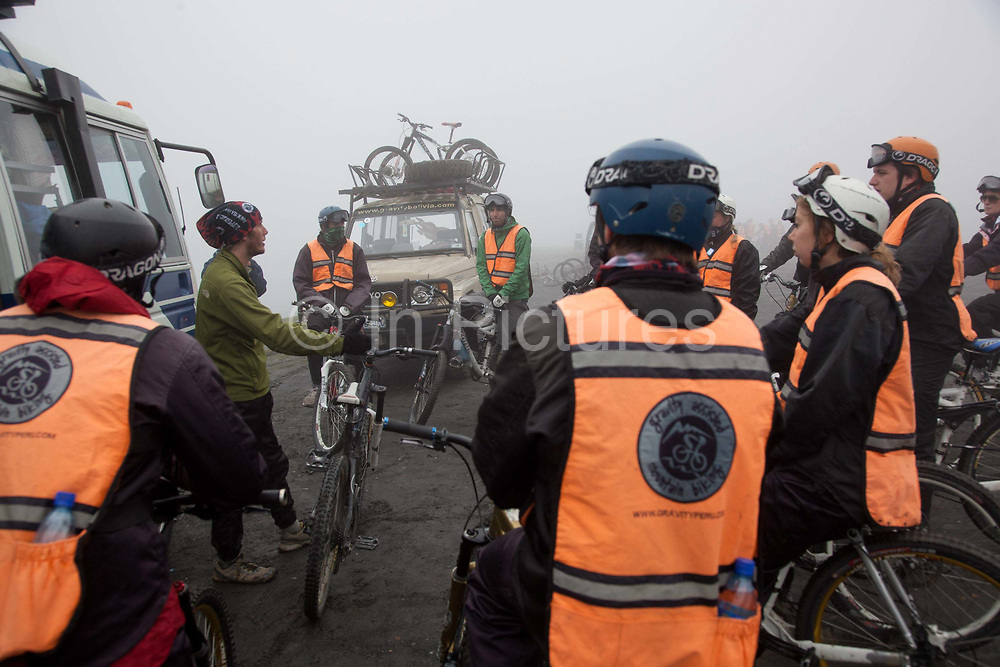 Travellers backpackers being briefed and preparing for their mountain bike ride on 'the World's most dangerous road' down to Coroico in the Yungas, La Paz province, Bolivia.