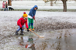 © Licensed to London News Pictures. 24/01/2021. London, UK. Kids enjoy cracking the ice on a frozen pond in Richmond Park South West London this morning. A chilly day ahead is forecast for the South East with the Met Office issuing a yellow weather warning for snow and ice for today with disruption to travel as the cold weather continues. Photo credit: Alex Lentati/LNP<br /> <br /> *Permission Granted*