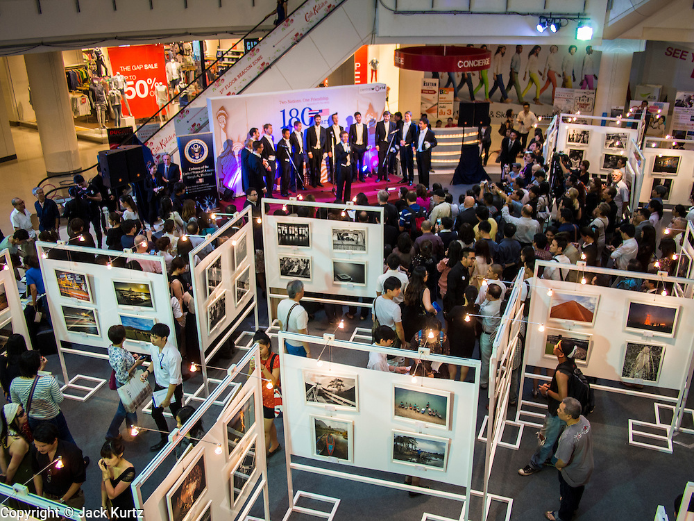 """19 JULY 2013 - BANGKOK, THAILAND:   People walk through the photo exhibit while the Yale Whiffenpoofs, one of the best-known collegiate a cappella groups in the world perform in CentralWorld in Bangkok Friday. Founded in 1909, the """"Whiffs"""" began as a senior quartet that met for weekly concerts at Mory's Temple Bar, the famous Yale tavern. The Bangkok stop was a part of their 2013 world tour and was sponsored by the US Embassy. They sang at the opening of a photo exhibit that marked 180 years of friendly diplomatic relations between Thailand and the United States.   PHOTO BY JACK KURTZ"""