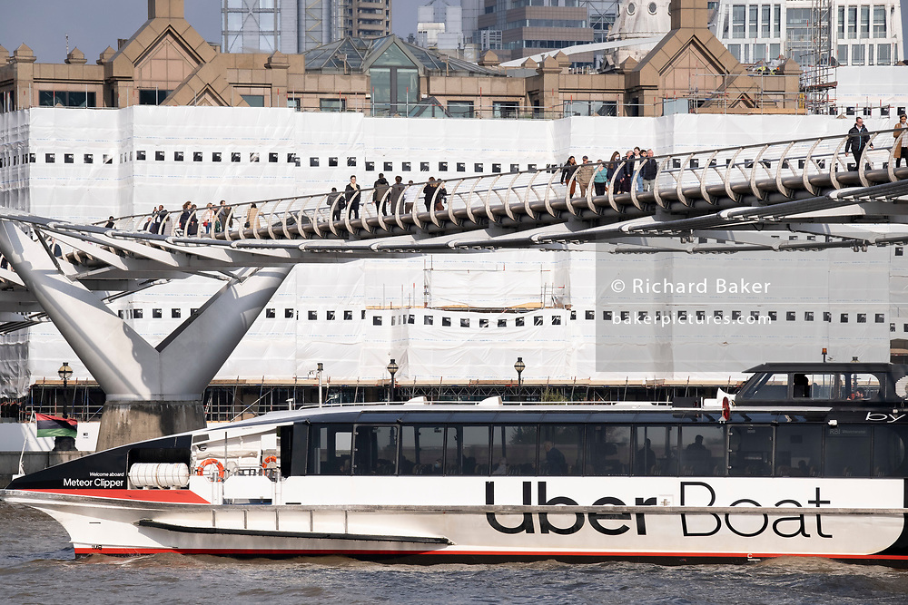 Uber Boat's 'Meteor Clipper' passes beneath the Millennium Bridge and passes corporate properties undergoing revelopment, overlooking the Thames, on 19th October 2021, in London, England. Thames Clippers operate a fleet of 20 boats on the River Thames, with departures from 23 piers across London from Putney to Woolwich.
