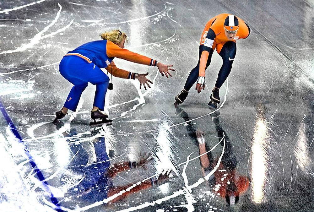 Italie, Turijn, 24-02-2006<br /> Olympische Winterspelen.<br /> Schaatsen, 10.000 meter, Heren.<br /> Coach Ingrid Paul komt vingers tekort om Bob de Jong die ver onder het beginschema rijdt, z'n tussentijd aan te geven. De Jong zal goud winnen met deze rit.<br /> Foto: Klaas Jan van der Weij / Sportstation <br /> Rie Cramerstraat 17<br /> 1183 CP Amstelveen<br /> Tel : 06-51433029