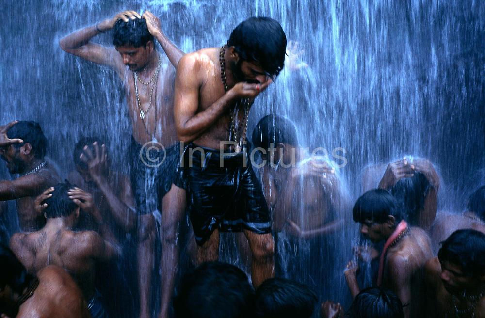Followers of the Shiva sect of Hinduism ritually bathe at a Hindu Bathing festival at Courtalam waterfall, Tamil Nadu, India