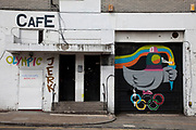 Olympic birdz graffiti by artist Ronzo. This subversive street art painting in Dalston in East London, UK, shows a pigeon defecating on the Olympic rings.