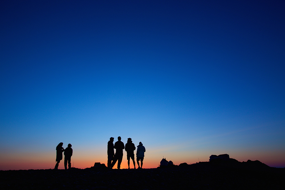 Silhouette of friends drinking and socialising at the Ecrehous off the coast of Jersey, at sunset