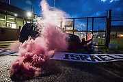 Two Palestine Action activists, one holding a smoke grenade, are locked onto a vehicle to block an entrance to the Instro Precision factory in Discovery Park on 4th October 2021 in Sandwich, United Kingdom. Instro Precision is a subsidiary of Israels largest publicly-traded arms company Elbit Systems supplying high precision military equipment and Palestine Action contends that Instro Precision equipment has been used by the Israeli military against the population of Gaza.