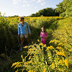 A woman and her five year-old daughter walk in a field at the Pell Farm in Grafton, Massachusetts.