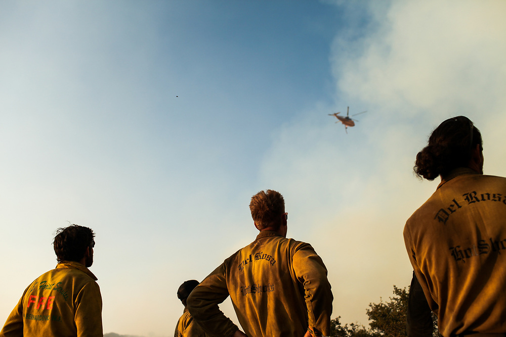 Members of the Del Rosa Hotshots watch as a helicopter prepares to drop water over a mountainside during the Whittier Fire in Santa Barbara County east of Goleta, California, Wednesday, July 12, 2017.