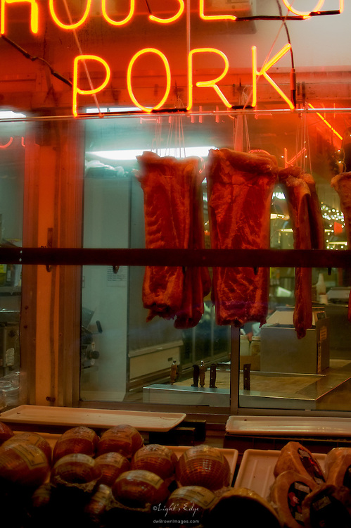 Pork ribs hang in a butcher's window on 9th St. in the Italian Market of Philly, early, prior to opening.