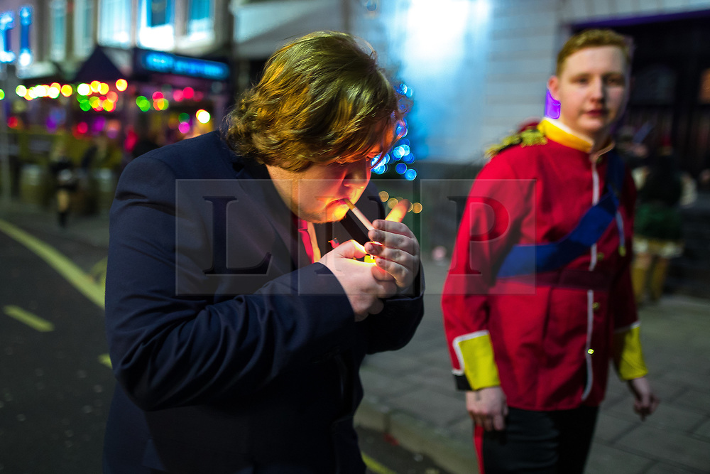 © Licensed to London News Pictures . 27/12/2017. Wigan, UK. Donald Trump lights a cigarette. Revellers in Wigan enjoy Boxing Day drinks and clubbing in Wigan Wallgate . In recent years a tradition has been established in which people go out wearing fancy-dress costumes on Boxing Day night . Photo credit: Joel Goodman/LNP