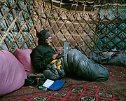 "Paul working on his computer in a yurt. Camp at a Wakhi high pasture names ""Warm"", below Garumdee Pass. Guiding and photographing Paul Salopek while trekking with 2 donkeys across the ""Roof of the World"", through the Afghan Pamir and Hindukush mountains, into Pakistan and the Karakoram mountains of the Greater Western Himalaya."