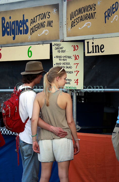 25 April 2014. New Orleans, Louisiana.<br /> A couple wait for food at the New Orleans Jazz and Heritage Festival. <br /> Photo; Charlie Varley/varleypix.com