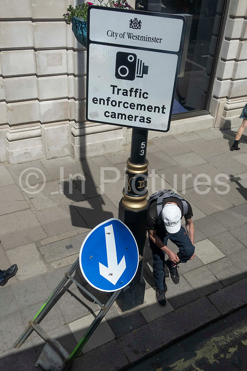 An aerial view of a male pedestrian who bends down to adust his trouser leg beside a traffic enforcement cameras sign on Piccadilly, on 27th May 2021, in London, England.