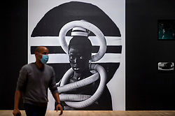 "© Licensed to London News Pictures. 03/11/2020. LONDON, UK.  A staff member next to a self-portrait ""Sebenzile, Parktown"", 2016, by Zanele Muholi. Preview of the first major UK exhibition by South African visual activist Zanele Muholi at Tate Modern.  260 photographs document black lesbian, gay, trans, queer and intersex lives in South Africa.  The show runs 5 November to 7 March 2021, but will be interrupted by England's coronavirus pandemic lockdown currently due to last 5 November to 2 December.  Photo credit: Stephen Chung/LNP"