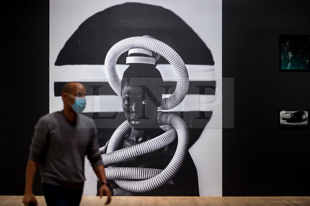 """© Licensed to London News Pictures. 03/11/2020. LONDON, UK.  A staff member next to a self-portrait """"Sebenzile, Parktown"""", 2016, by Zanele Muholi. Preview of the first major UK exhibition by South African visual activist Zanele Muholi at Tate Modern.  260 photographs document black lesbian, gay, trans, queer and intersex lives in South Africa.  The show runs 5 November to 7 March 2021, but will be interrupted by England's coronavirus pandemic lockdown currently due to last 5 November to 2 December.  Photo credit: Stephen Chung/LNP"""
