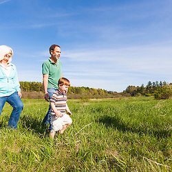 A man and woman walk with their three year-old grandson in a field in Durham, New Hampshire.