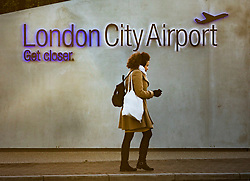 © Licensed to London News Pictures. 12/02/2018. London, UK. A passenger walks past an entrance to London City Airport which remains closed after a World War II era bomb was found in The River Thames during routine work on nearby King V Dock. Police have evacuated nearby residents, closed the airport and set up a 214-metre exclusion zone. Photo credit: Peter Macdiarmid/LNP