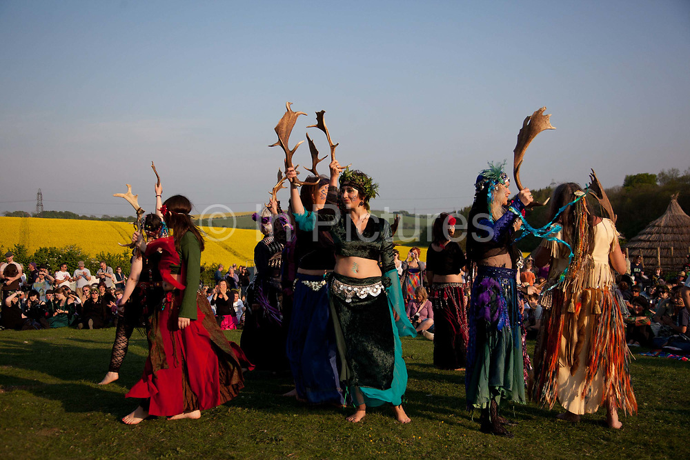 People dressed in Morris dancing attire perform for crowds visitors, english traditions. The annual Beltane celebrations at Butser ancient farm, Hampshire, marking the beginning of the British summer.