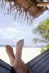 Low section view of a man relaxing on hammock, Tangalle, South Province, Sri Lanka