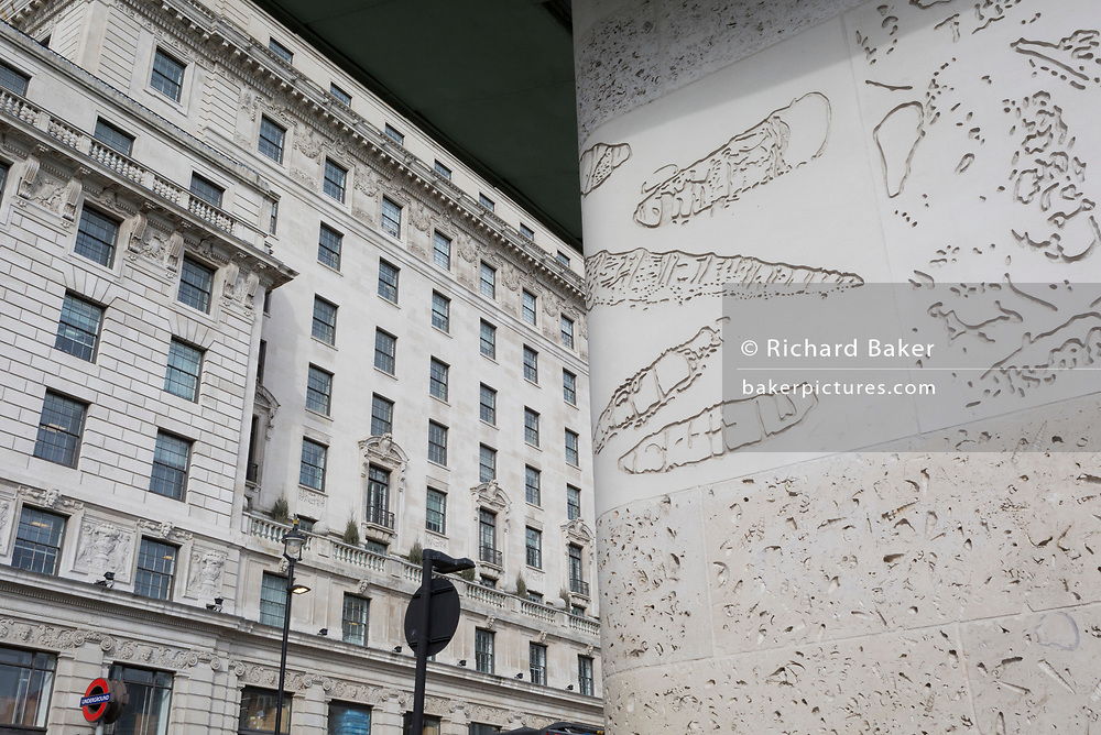 The tall architecture of office spaces above Green Park Underground station on Piccadilly (left) and the wall of the station opposite the road, that features the imprints of sea creatures and sea shells indented into the concrete, on 25th February 2020, in London, England.