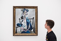 "Boy looking at painting by Pablo Picasso "" Sitzende Frau, 1941"" at Pinakothek Museum in Munich Germany"