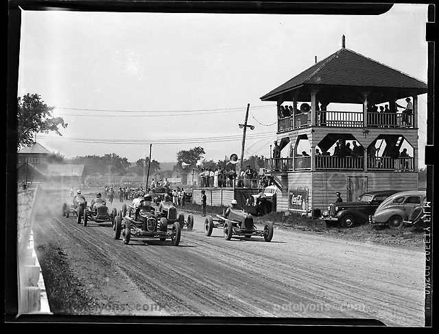 Start of a dirt car heat race at Altamont Fairgrounds near Albany, NY. Photo taken in 1938 with medium-format view camera by Ozzie Lyons. Announcer at microphone on second level of pagoda COULD be legendary newsman Chris Ekonomaki, who did call races here.