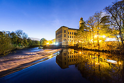 © Licensed to London News Pictures. 29/10/2017. Saltaire UK. Salts Mill reflects into the River Aire at Dawn this morning in the World Heritage Site of Saltaire village in Yorkshire. Photo credit: Andrew McCaren/LNP