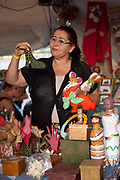 Brazilian Gaucha woman selling showing traditional Gaucho crafts made from wood, figurines, on a stall at Reponte da Cancao music festival and song competition in Sao Lorenzo do Sul, RIo Grande do Sul, Brazil.